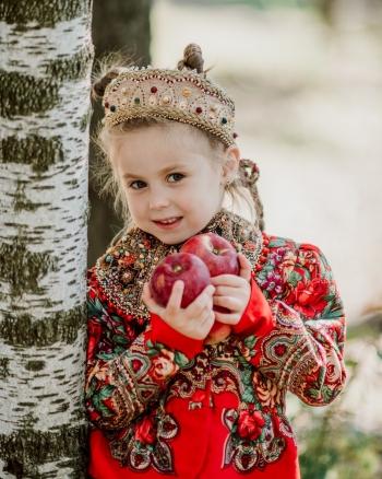 Девочка в диадеме коруне с яблоками у дерева